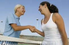 Två kvinnliga tennisspelare som skakar handen över sikt för netto låg vinkel för tennisbana Arkivfoton
