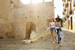 Två kvinnliga vänner på ferie som går med resehandboken, Ibiza royaltyfri bild
