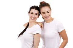 Två kvinnliga vänner på vit bakgrund Royaltyfri Fotografi