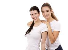Två kvinnliga vänner på vit bakgrund Royaltyfri Bild