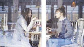 Två kvinnliga vänner som möter i ett kafé för att tala arkivfoton