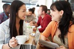 Två kvinnliga vänner som möter i upptagen coffee shop Fotografering för Bildbyråer