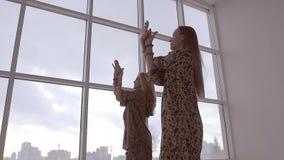 Två kvinnliga vänner som tillsammans gör yoga mot fönsterbakgrund stock video