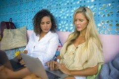 Två kvinnliga vänner som tillsammans utomhus arbetar på det kalla kafét med bärbar datordatoren, en flickacaucasian, det annat af arkivfoton