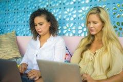 Två kvinnliga vänner som tillsammans utomhus arbetar på det kalla kafét med bärbar datordatoren, en flickacaucasian, det annat af royaltyfri foto