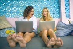 Två kvinnliga vänner som tillsammans utomhus arbetar på det kalla kafét med bärbar datordatoren, en flickacaucasian, det annat af arkivfoto