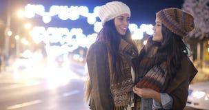 Två kvinnliga vänner som tycker om en natt på staden Fotografering för Bildbyråer