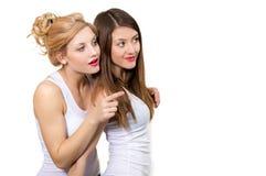 Två kvinnliga vänner som visar på kopieringsutrymme på vit Arkivfoton