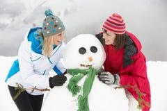 Två kvinnligvänner som bygger snowmanen skidar på, ferie fotografering för bildbyråer