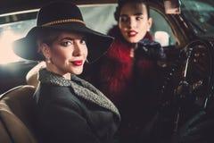 Två kvinnor bland in en retro bil i garage Royaltyfri Foto