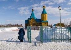 Två kvinnor bugade ner framme av den ortodoxa kyrkan Arkivfoto