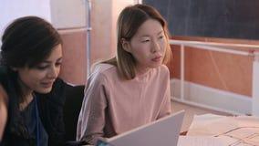 Två kvinnor diskuterar aktivt uppgifter på kurs genom att använda bärbara datorn lager videofilmer