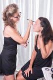 Två kvinnor, en sätter på det annat sminket royaltyfria foton