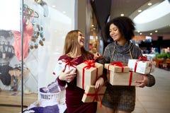 Två kvinnor för blandat lopp med gåvaaskar i händer nära storewindow Mång- etniska flickor som ler med gåvor på jul royaltyfri foto