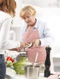 Två kvinnor som lagar mat i kök Arkivbilder