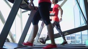 Två kvinnor går på löparbanor nära panorama- fönster arkivfilmer