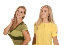 Två kvinnor gör grön gult ställningsleende arkivfoto