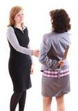 Två kvinnor gör handskakningen på av dem håll att baktala bak henne tillbaka Arkivbilder