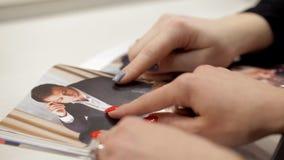 Två kvinnor håller ögonen på en tidskrift om skönhet stock video