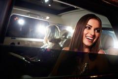 Två kvinnor i baksidan av en limo som fotograferas av paparazzi arkivbilder