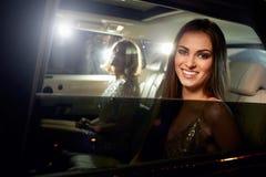 Två kvinnor i baksidan av en limo som fotograferas av paparazzi royaltyfri foto