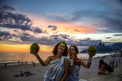 Två kvinnor i dräkterna av grekiska gudinnor på bakgrunden av den härliga solnedgången på Ipanema sätter på land, Carnaval arkivbilder