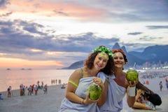 Två kvinnor i dräkterna av grekiska gudinnor på bakgrunden av den härliga solnedgången på Ipanema sätter på land, Carnaval royaltyfria bilder