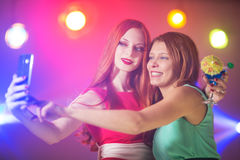 Två kvinnor i en nattklubb under strålkastaren med en coctail in arkivbilder