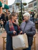 Två kvinnor i shoppinggallerian med påsen Fotografering för Bildbyråer