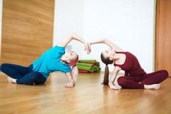 Två kvinnor i sportswearen som gör sträckning, övar på matt yoga Sunt uppehälle- och konditionbegrepp royaltyfri foto