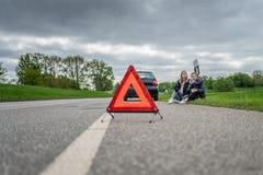Två kvinnor med bilsammanbrottet som sitter på vägrenen och den väntande på hjälpen arkivfoto