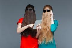 Två kvinnor med dolda framsidor genom att använda minnestavlan och mobiltelefonen Arkivfoto