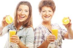 Två kvinnor med orange fruktsaft Arkivbilder