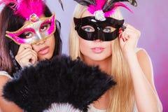 Två kvinnor med venetian maskeringar för karneval Arkivbild