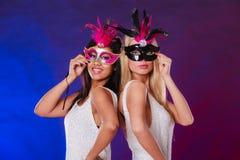 Två kvinnor med venetian maskeringar för karneval Arkivbilder