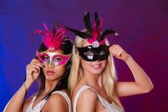 Två kvinnor med venetian maskeringar för karneval Arkivfoto