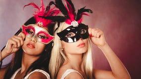 Två kvinnor med venetian maskeringar för karneval Fotografering för Bildbyråer