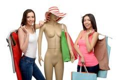 Två kvinnor, når shoppa med påsar och skyltdockan Arkivbilder