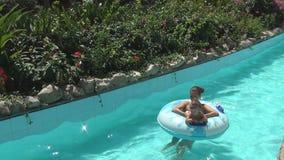 Två kvinnor och behandla som ett barn leende och att sväva på simningcirklar på en långsam flod i trädgård stock video