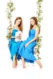 Två kvinnor på en gunga på vit bakgrund Royaltyfri Foto