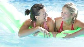 Två kvinnor på ferie i simbassäng lager videofilmer