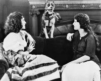 Två kvinnor på soffan med hunden (alla visade personer inte är längre uppehälle, och inget gods finns Leverantörgarantier att det arkivbild