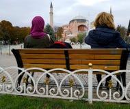 Två kvinnor sitter framme av springbrunnen av den sultanahmetfyrkanten och blicken på Hagiaen Sophia arkivbild