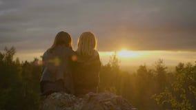 Två kvinnor sitter på stenen arkivfilmer