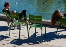 Två kvinnor sitter på stolar i solen, långa skuggor som fördjupa från stolarna Royaltyfri Bild