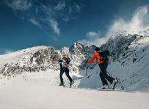 Två kvinnor skidar fotgängare går upp på bergöverkanten Arkivfoto