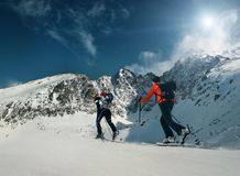 Två kvinnor skidar fotgängare går upp på bergöverkanten Arkivbilder