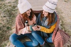 Två kvinnor skrattar tillsammans, medan de dricker en kopp av varm buljong royaltyfri fotografi