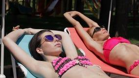 Två kvinnor solbadar nära simbassängen stock video