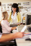 Två kvinnor som är funktionsdugliga på skrivbord i upptaget idérikt kontor Arkivbilder